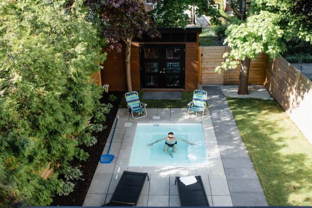 Homme qui se baigne dans la mini piscine installée dans son jardin